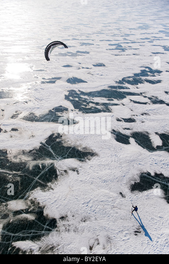 A snowkiter catching the wind on the frozen Missouri River in North Dakota. - Stock Image