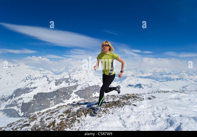 Woman jogging across snowy mountains. - Stock-Bilder
