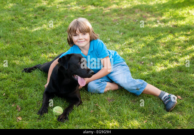 Boy (6-7) lying on lawn with dog - Stock Image