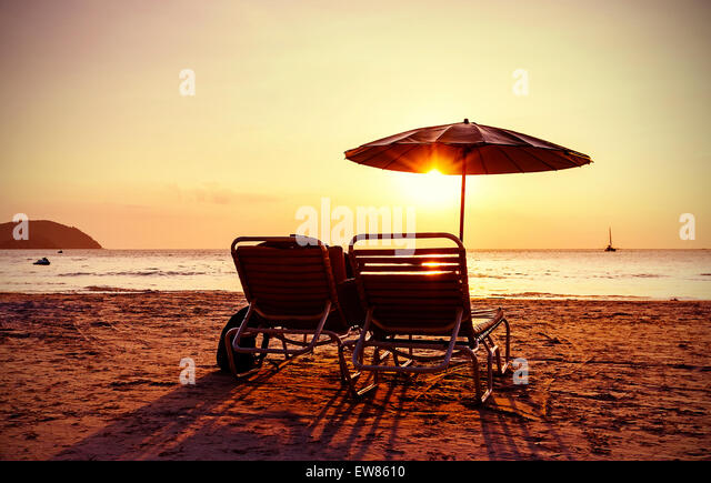 Vintage instagram stylized beach chairs and umbrella at sunset. Concept for holidays and relaxation. - Stock-Bilder