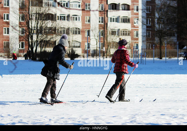 two child goes skiing on the inner court of the school during physical education classes - Stock Image