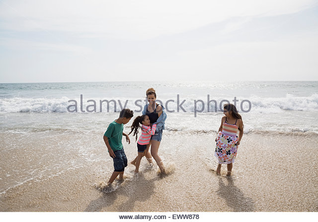 Family playing in ocean surf - Stock Image
