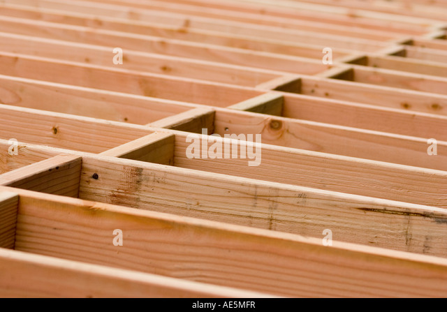 Wood blocking in a staggered pattern between floor joists at a residential building construction project - Stock Image