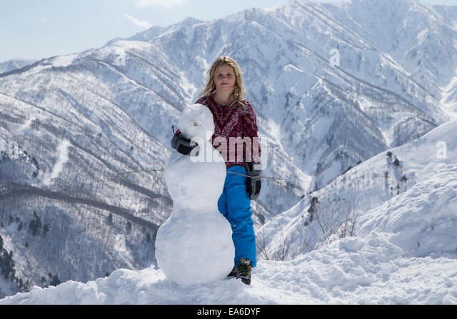 Girl (10-11) posing with snowman - Stock Image