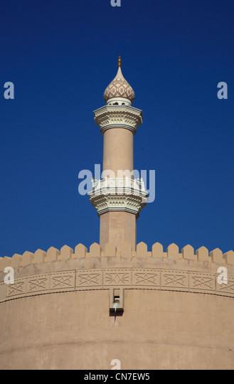 Moscheeturm und Brüstung des alten Forts von Nizwa. Nizwa ist das Zentrum des omanischen Kernlandes. Die Oasenstadt - Stock-Bilder