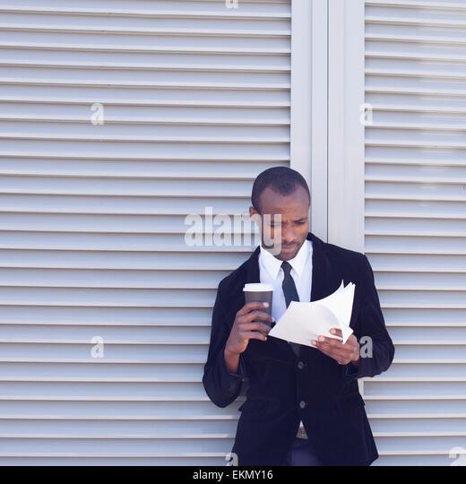 stylish black man documents handling outdoors - Stock Image