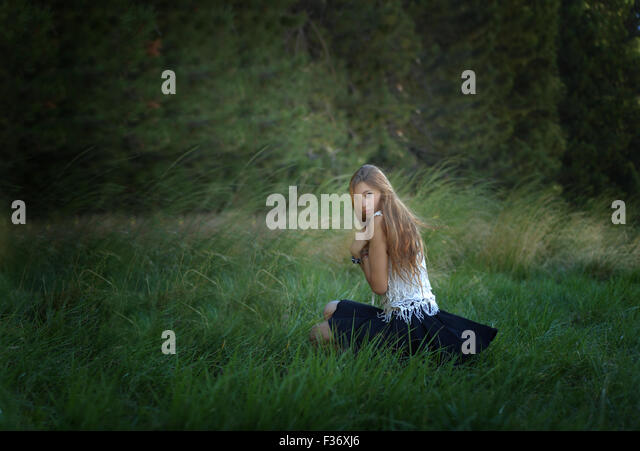 mysterious girl with long hair in the forest green grass - Stock Image