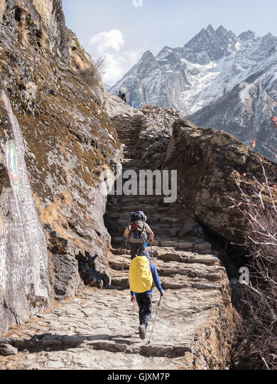 Backpackers make their way up steps as they journey through Nepal's Everest Base Camp in the middle of winter - Stock Image
