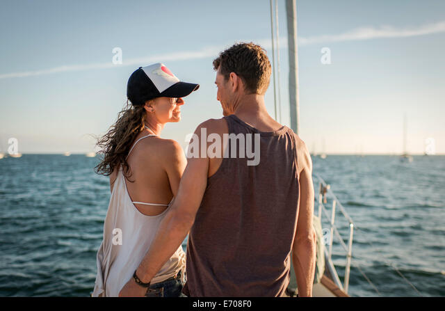 Couple on boat in ocean, rear view - Stock Image