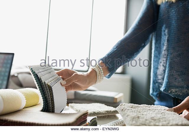 Interior designer examining carpet swatches - Stock-Bilder