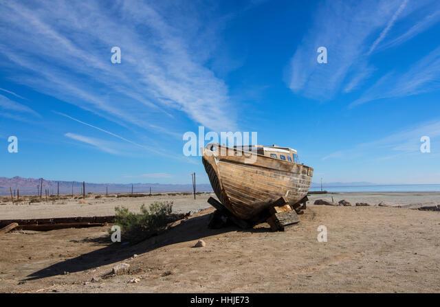 Desert landscape abandoned boat at Bombay Beach at the Salton Sea in California desert - Stock Image