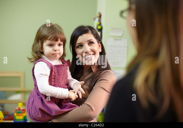 Caucasian female teacher and mom with baby girl talking in kindergarten. Horizontal shape, focus on background - Stock Image