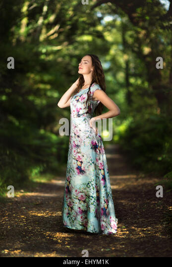 Teenage girl standing on a path in the forest - Stock Image