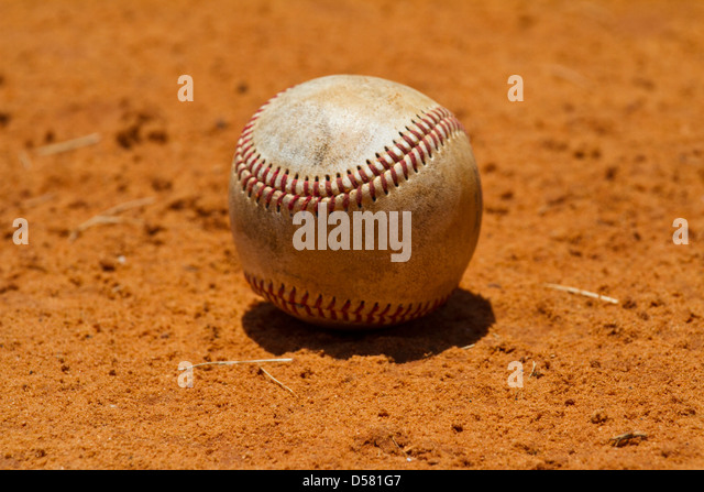 Baseball lying in a field - Stock Image