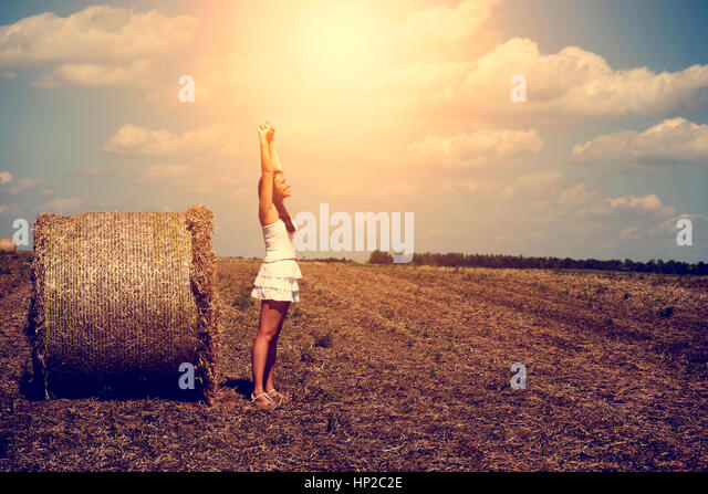 Happy woman and straw bale - Stock Image