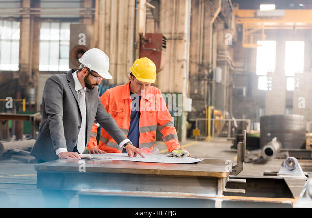 Manager and steel worker engineer reviewing blueprints in factory - Stock Image