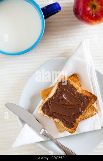 Breakfast with Chocolate Spread on Toast and Milk - Stock Image