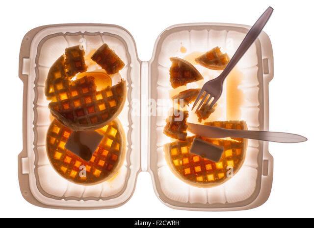 Looking straight down on waffles with butter and syrup in a plastic container with a fork and knife, half-eaten - Stock-Bilder
