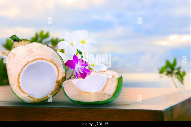 twon half of green coconut water on top  wood table with tropical orchid flowers and white  frangipani bouquet decorated - Stock Image