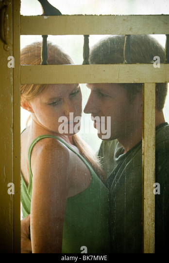 Young couple seated on porch viewed through screen door - Stock-Bilder
