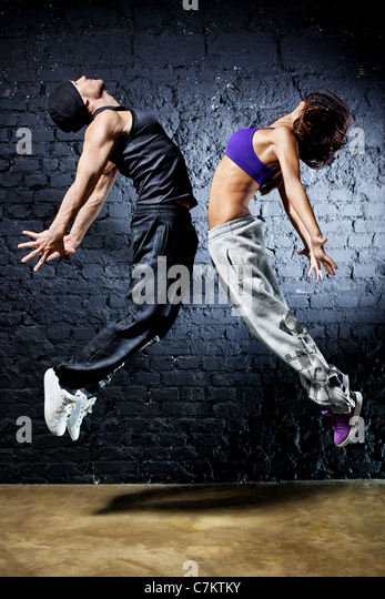 Young dancer couple jumping. On wall background. - Stock Image