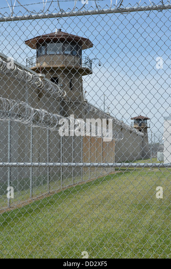 American maximum security prison guard tower and perimeter wall. Tower officers are armed with rifles and shotguns. - Stock Image