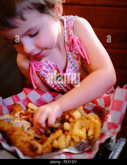 Cute Girl Having Chicken Fingers At Restaurant - Stock Image
