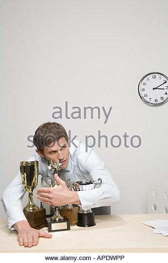 Businessman hugging trophies - Stock Image