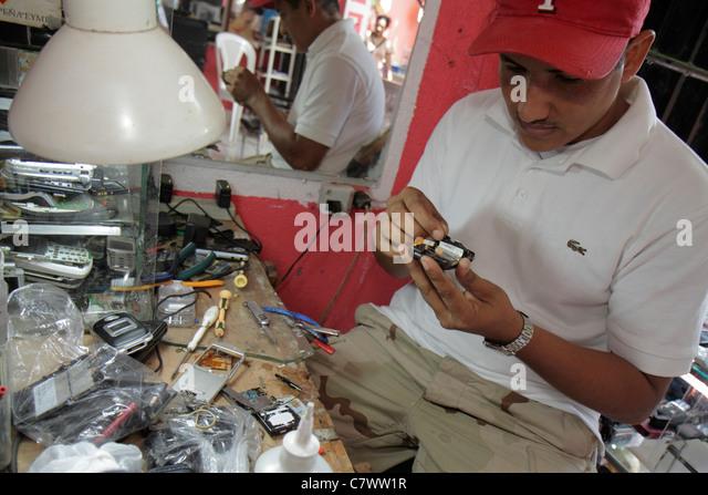 Nicaragua Managua Mercado Roberto Huembes market marketplace electronic repair shop workshop technician mobile cell - Stock Image