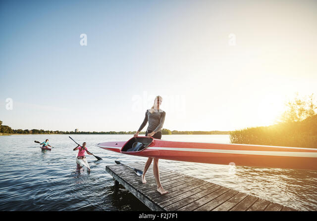 Rowing team after training getting out of the water - Stock Image