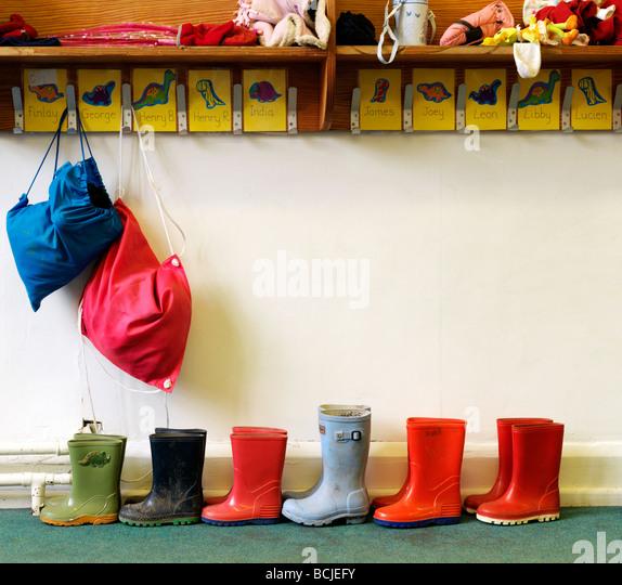 childrens wellington boots in school near pegs - Stock-Bilder