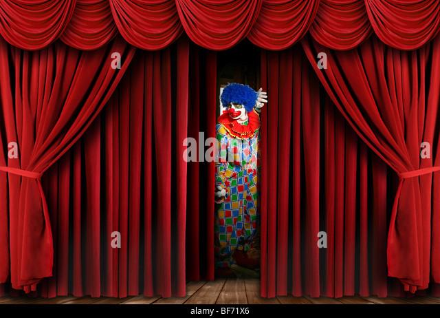Eerie Creepy Clown Looking Through Stage Curtain Drapes - Stock-Bilder