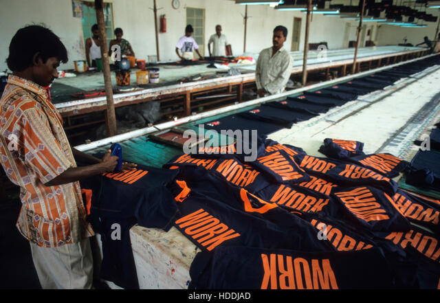INDIA, Tamil Nadu, Tirupur, textile factory, worker print T-shirts with the word WORK for export - Stock Image