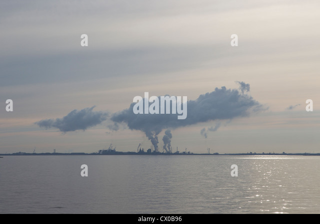 plume smoke horizon haze hazy sun sunshine sea sky water shimmer shimmering sunlight pollution carbon emissions - Stock Image