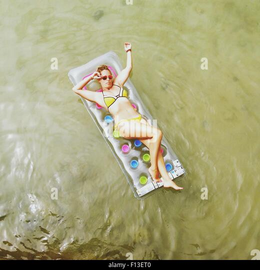 Overhead view of a woman lying on an inflatable mattress in the sea - Stock Image
