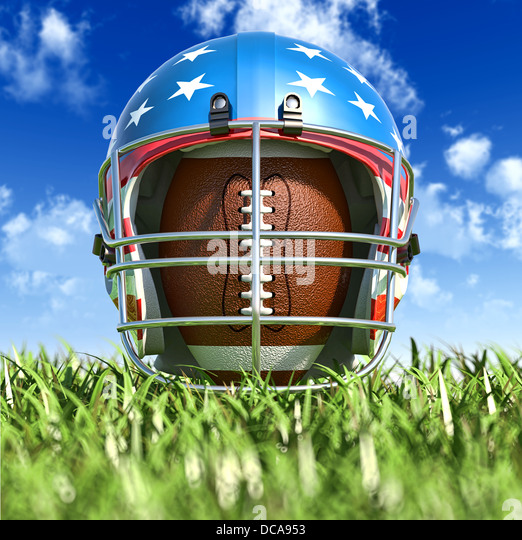 American football helmet over the oval ball, on the grass. Frontal Close up view, from the ground level. With sky. - Stock Image