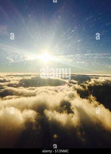 Looking out an airplane window at clouds and the sun. - Stock Image