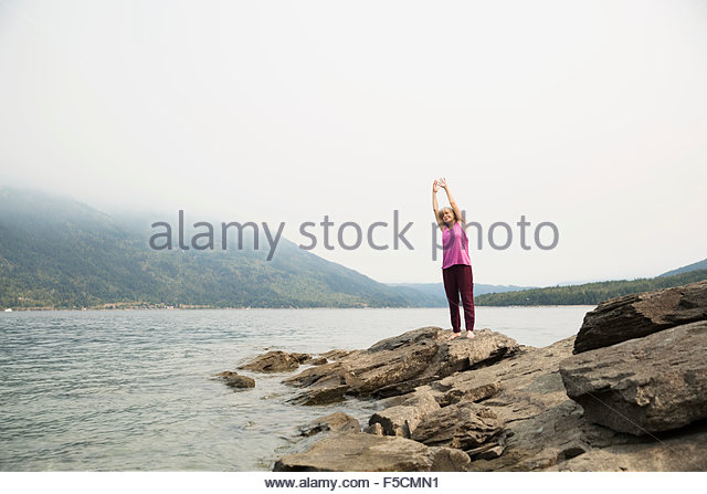 Mature woman practicing yoga on rock at lakeside - Stock Image