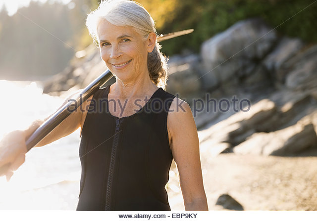 Portrait of senior woman in wetsuit on beach - Stock Image