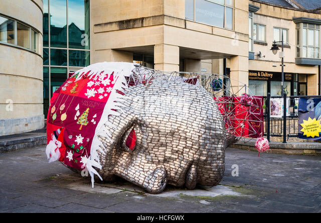 A civic sculptured metal head decorated for Christmas by local people - Stock Image