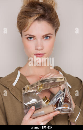Beautiful woman holding a make-up bag - Stock Image