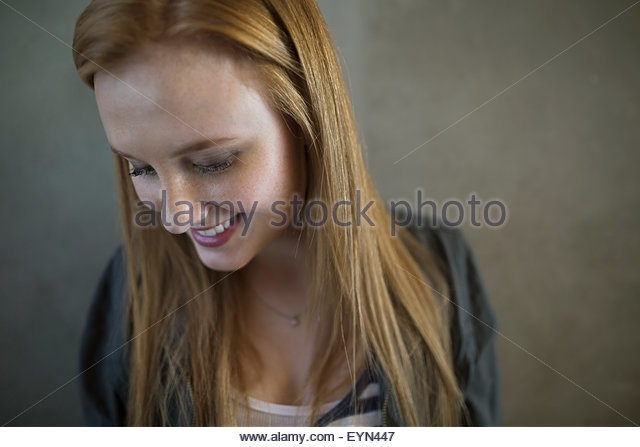 Portrait smiling young woman red hair looking down - Stock Image