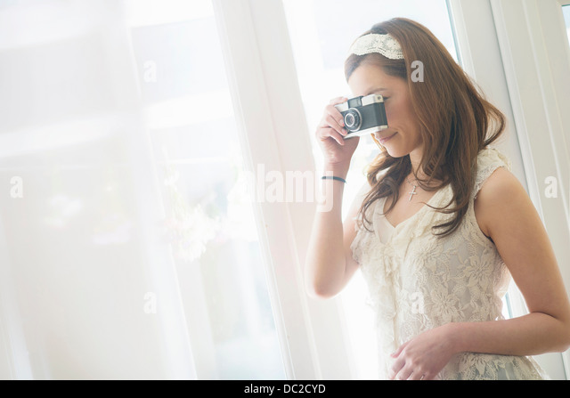 Woman looking through camera - Stock Image