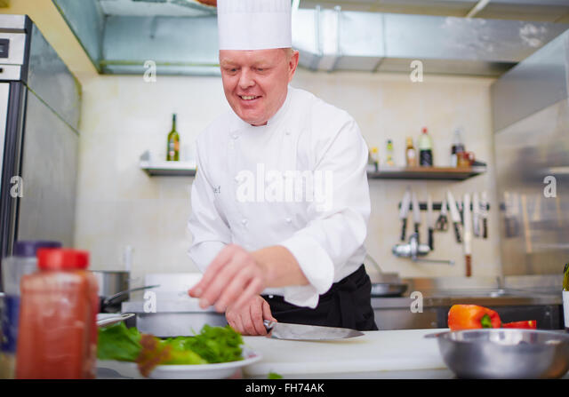 Chef cooking tasty food in the kitchen - Stock Image