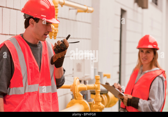 Process engineers talking on a walkie-talkie and taking meter reading - Stock Image