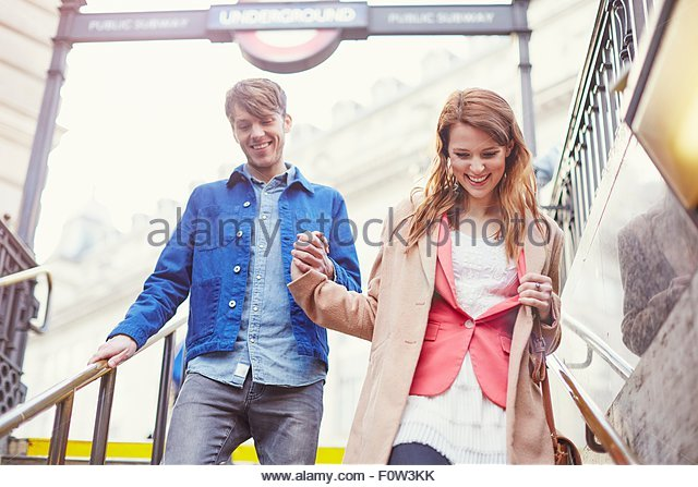 Couple moving down London underground stairway, London, UK - Stock Image