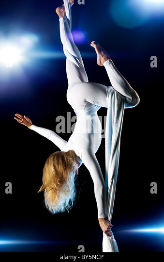 Young woman gymnast. On black background with flashes effect. - Stock-Bilder
