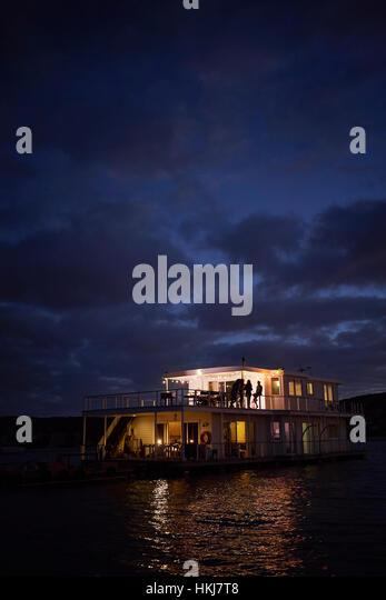 Summer houseboat illuminated on night ocean - Stock-Bilder