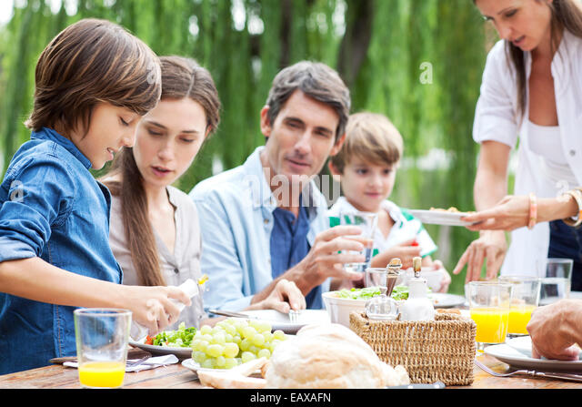 Family eating together at outdoor gathering - Stock-Bilder