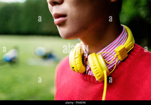 Midsection of young man with yellow headphones around neck at park - Stock Image